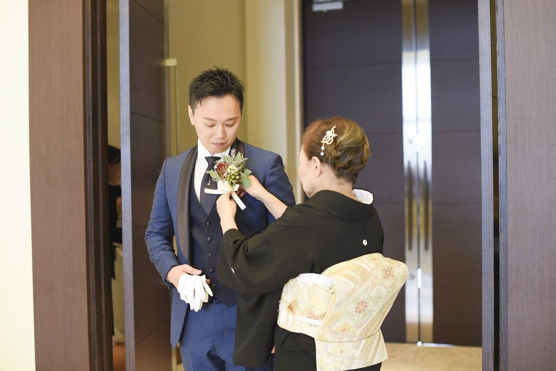 高松市の結婚式場アイルバレクラブでブートニアを新郎に付けるお母様