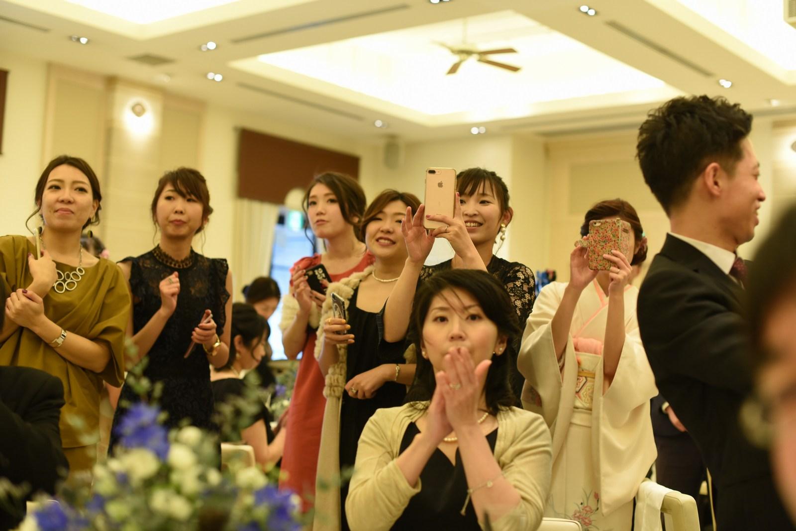 高松市の結婚式場アイルバレクラブでケーキ入刀シーンを撮るゲストの笑顔