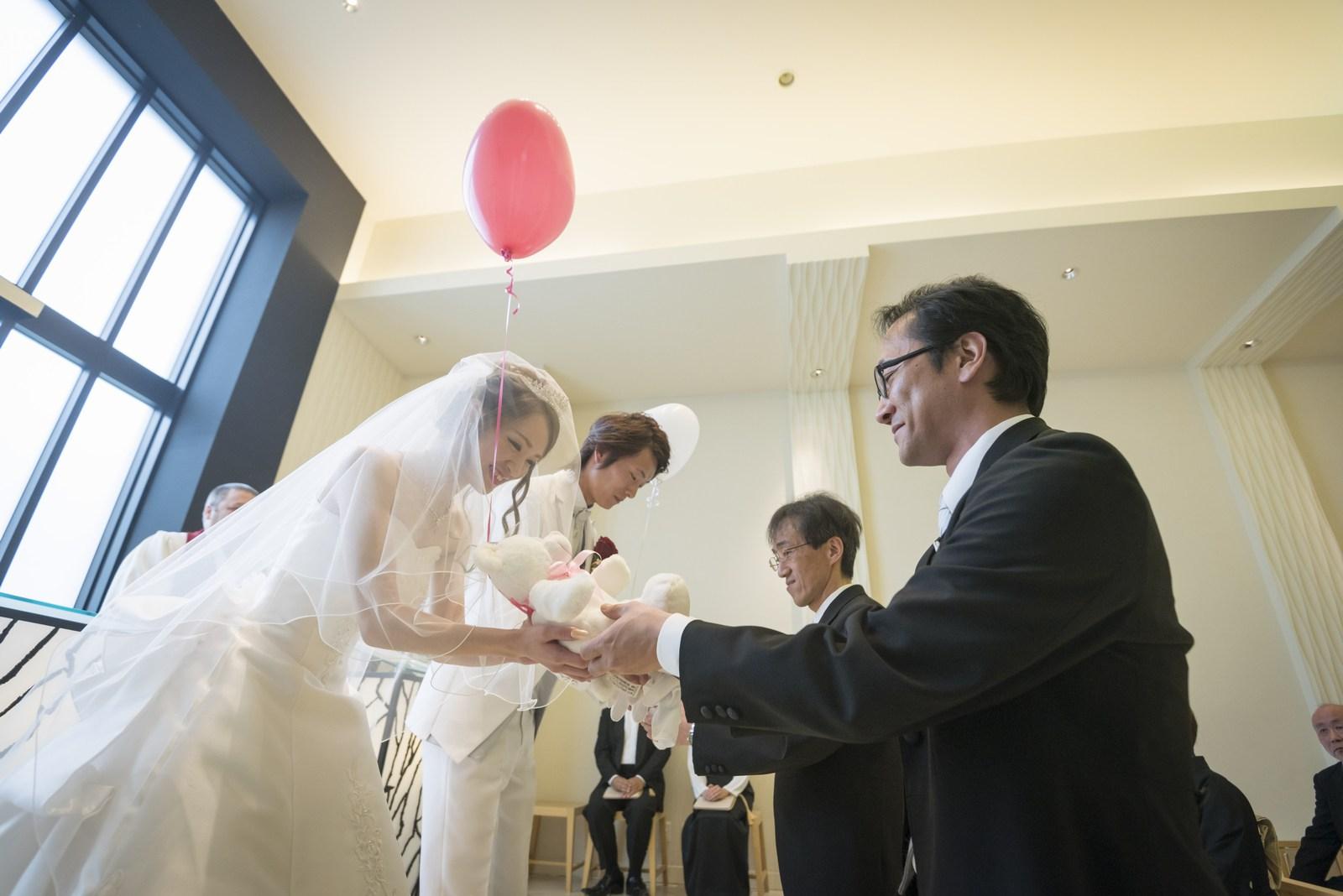 高松市の結婚式場アイルバレクラブの挙式でリングベアーを両家のお父様からお二人へ