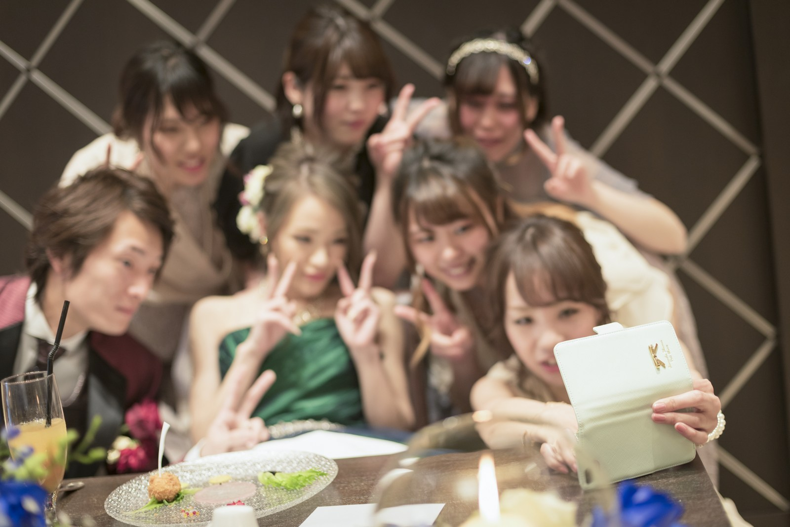 高松市の結婚式場アイルバレクラブのメインテーブルで新婦ゲストと自撮りをするお二人