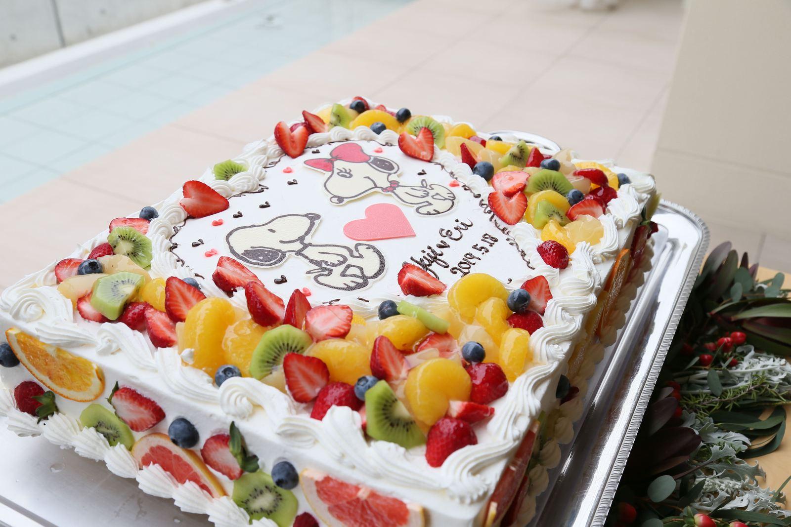 高松市の結婚式場アイルバレクラブのウェディングケーキ たくさんのフルーツとスヌーピーで飾り付けられたオリジナルケーキ